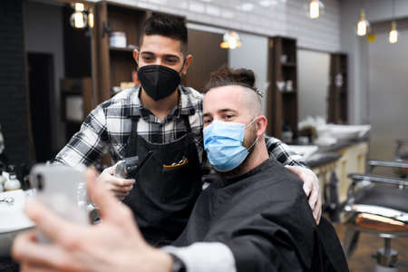 Man client taking selfie with haidresser in barber shop,  new normal concept.