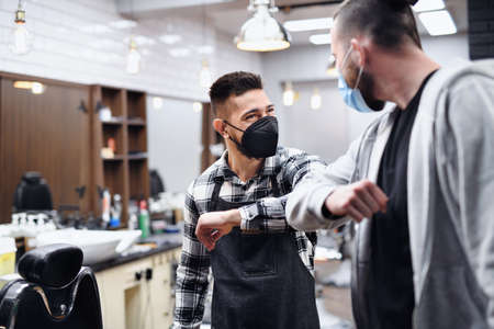 Man greeting haidresser with elbow bump in barber shop, new normal concept.