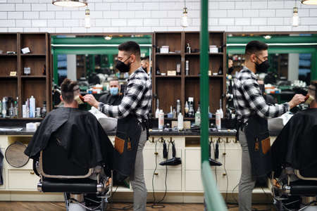 Man client visiting haidresser in barber shop,  new normal concept. Foto de archivo