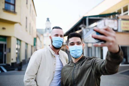 Men friends outdoors on street in town taking selfie,  new normal concept.