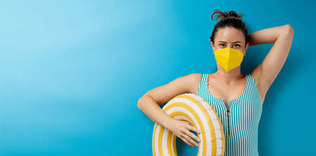Flat lay top view portrait of young woman with face mask, summer holiday, coronavirus and travel concept.