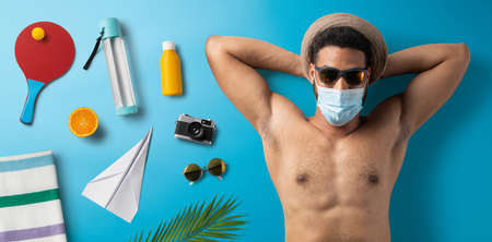 Flat lay top view portrait of young man with face mask, summer holiday, coronavirus and travel concept.