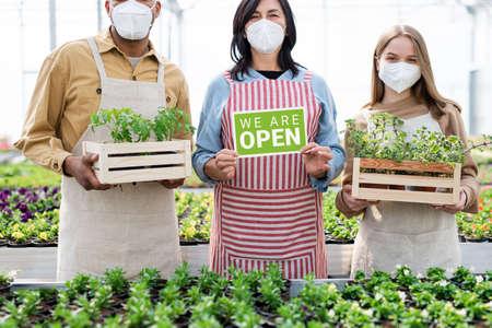 People working in greenhouse in garden center, store open after coronavirus lockdown.