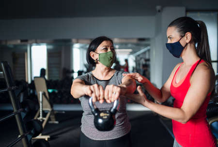 Senior woman with personal trainer doing exercise in gym, concept. Stock fotó