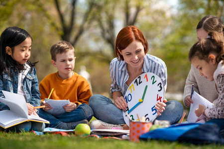 Teacher with small children sitting outdoors in city park, learning group education concept. 免版税图像