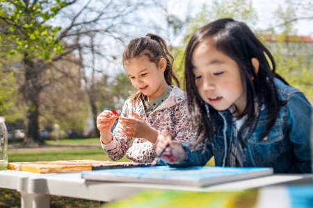 Small children painting pictures outdoors in city park, learning group education concept. 免版税图像
