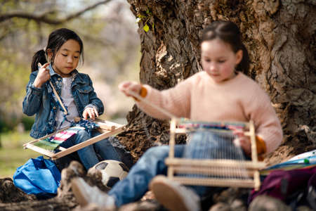 Small children with hand loom sitting outdoors in city park, learning group education concept.