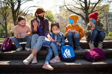 Teacher with small children sitting outdoors in city park, learning group education and virus concept. 免版税图像