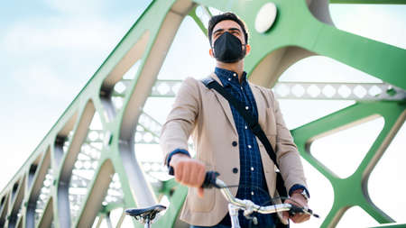 Low angle view of young business man commuter with bicycle going to work outdoors on bridge in city, virus concept.