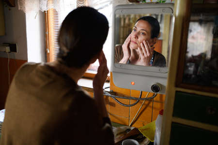 Poor mature woman looking in mirror in kitchen indoors at home, poverty concept.