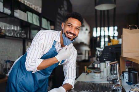 Portrait of waiter looking at camera in cafe, small business, virus and new normal concept.