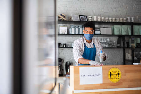 Waiter disinfecting surfaces in cafe, small business, virus and new normal concept. 免版税图像