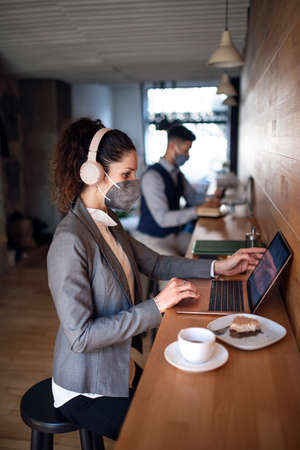 Business people with laptop working in cafe, small business, virus and new normal concept. 免版税图像