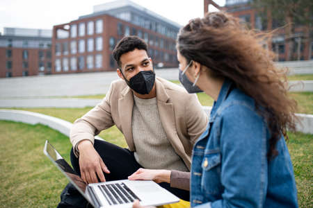 Man and woman with laptop working outdoors in park in city, virus concept.