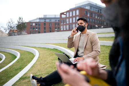 Man with laptop working outdoors in park in city, virus concept.