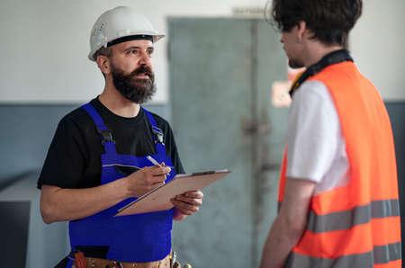Portrait of men workers with helmet indoors in factory, discussing issues. Reklamní fotografie