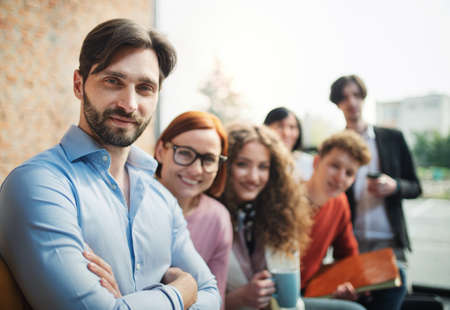 Portrait of young businessman with group of entrepreneurs indoors in office, looking at camera.
