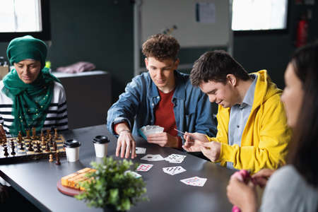 Group of people playing cards and board games in community center, inclusivity of disabled person. Reklamní fotografie