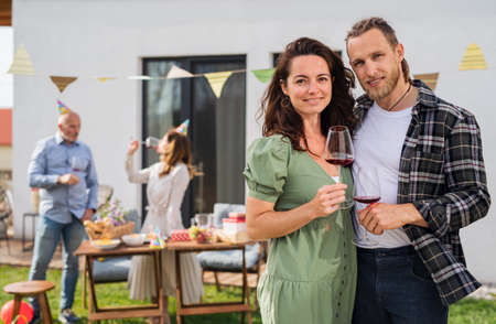 Young couple with wine outdoors in garden at home, birthday celebration party.