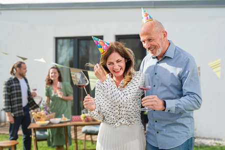 Mature couple with wine outdoors in garden at home, birthday celebration party.