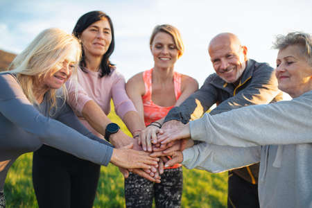 Group of seniors with sport instructor stacking hands after exercise outdoors in nature, active lifestyle.