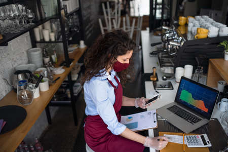 Frustrated coffee shop manager calculating figures in cafe, small business and new normal concept.