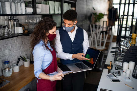 Coffee shop manager discussing issues with waitress in cafe, small business and new normal concept.