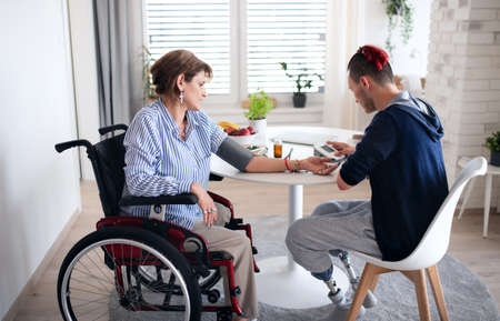 Disabled people in wheelchair sitting at the table indoors at home, measuring blood pressure.