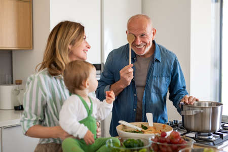 Senior couple with granddaughter indoors at home, cooking.