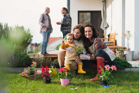 Happy multigeneration family outdoors planting flowers in garden at home, gardening concept. Reklamní fotografie