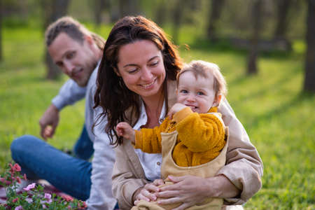 Happy young parents with small baby daughter sitting on grass in nature, relaxing. Reklamní fotografie