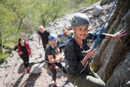 Group of seniors with instructor climbing rocks outdoors in nature, active lifestyle. Reklamní fotografie