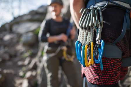 Unrecognizable instructor with harness and carabiners climbing rocks with seniors outdoors in nature, active lifestyle. Reklamní fotografie