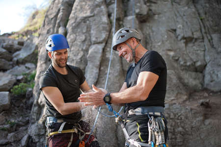 Senior man with instructor using chalk before climbing rocks outdoors in nature, active lifestyle.