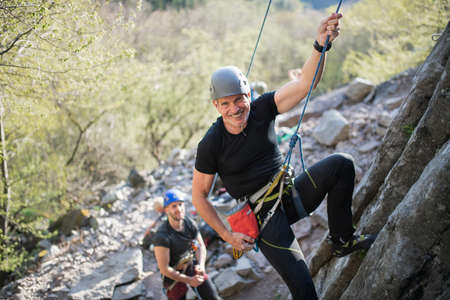 Senior man with instructor climbing rocks outdoors in nature, active lifestyle.