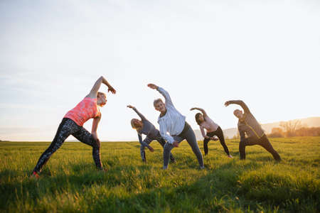 Group of seniors with sport instructor doing exercise outdoors in nature at sunset, active lifestyle.