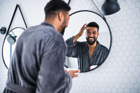 Young man applying cream on face indoors at home, morning or evening routine concept.