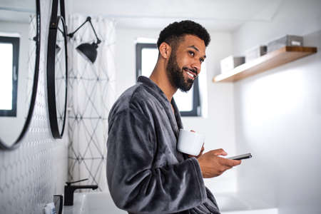 Young man with coffee and bathrobe indoors in bathroom at home, morning routine concept. 免版税图像
