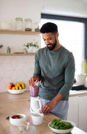 Young man preparing healthy breakfast indoors at home, making milk shake.