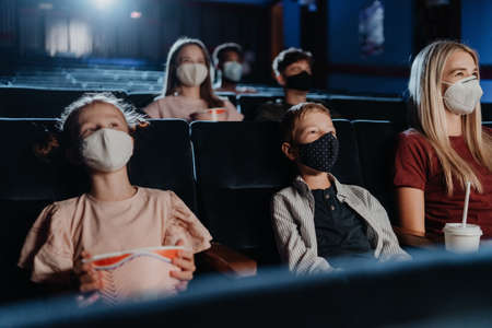 Mother with happy small children watching film in the cinema, virus concept. 免版税图像