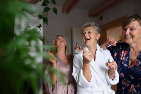 Happy senior women friends in bathrobes having fun indoors at home, selfcare concept.