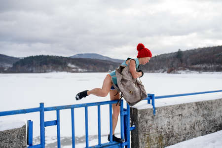 Active senior woman in swimsuit crossing fence outdoors in winter, cold therapy concept.