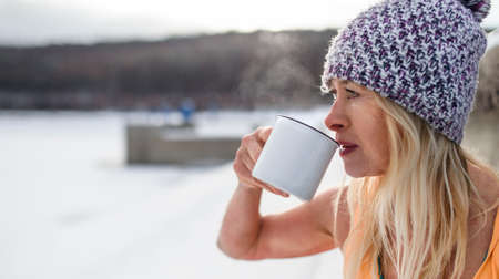 Portrait of active senior woman in sports clothes drinking tea outdoors in winter, cold therapy concept. Copy space.