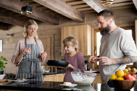Family with small daughter cooking indoors, winter holiday in private apartment.