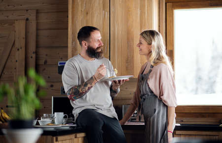 Mature couple having fun when cooking and eating indoors in kitchen.