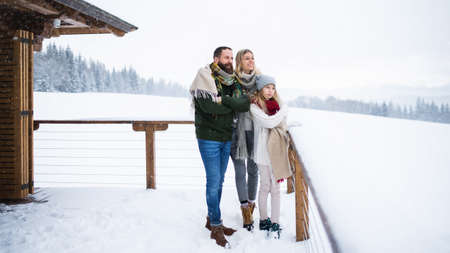 Family with small daughter on terrace outdoors, holiday in winter nature.