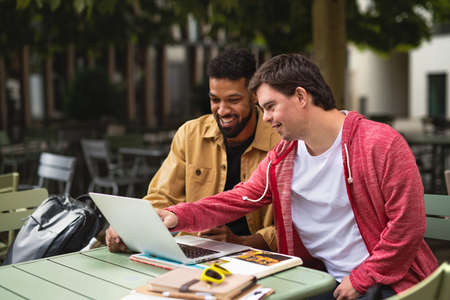 Young man with Down syndrome with his mentoring friend sitting outdoors in cafe using laptop.
