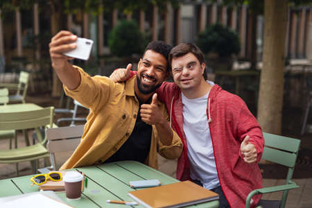 Young man with Down syndrome and his mentoring friend sitting and taking selfie outdoors in cafe