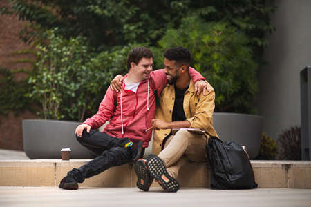 Happy young man with Down syndrome and mentoring friend sittingwith arms around outdoors