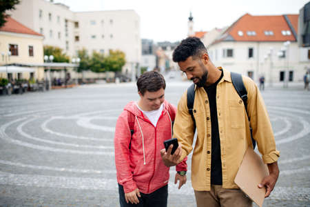Young man with Down syndrome and his mentoring friend with smartphone walking and talking outdoors